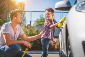 dad and son cleaning car