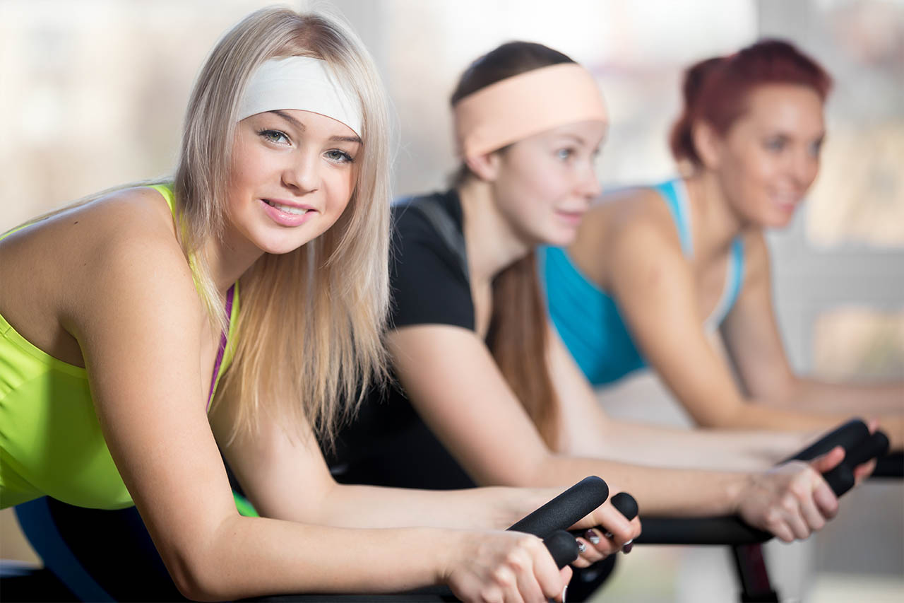 The group of women enjoys their workout at the exercise bike.