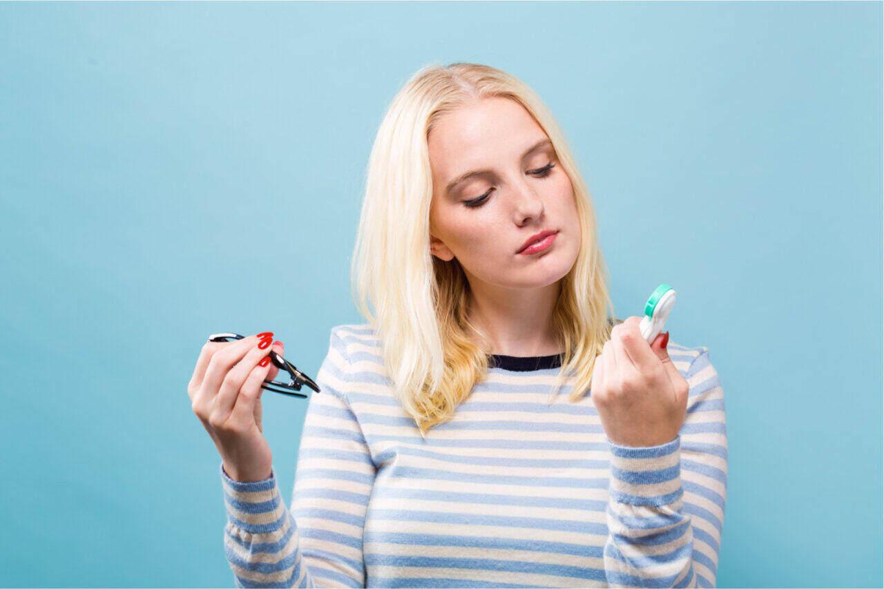 A girl battling in selecting contact lenses vs. glasses
